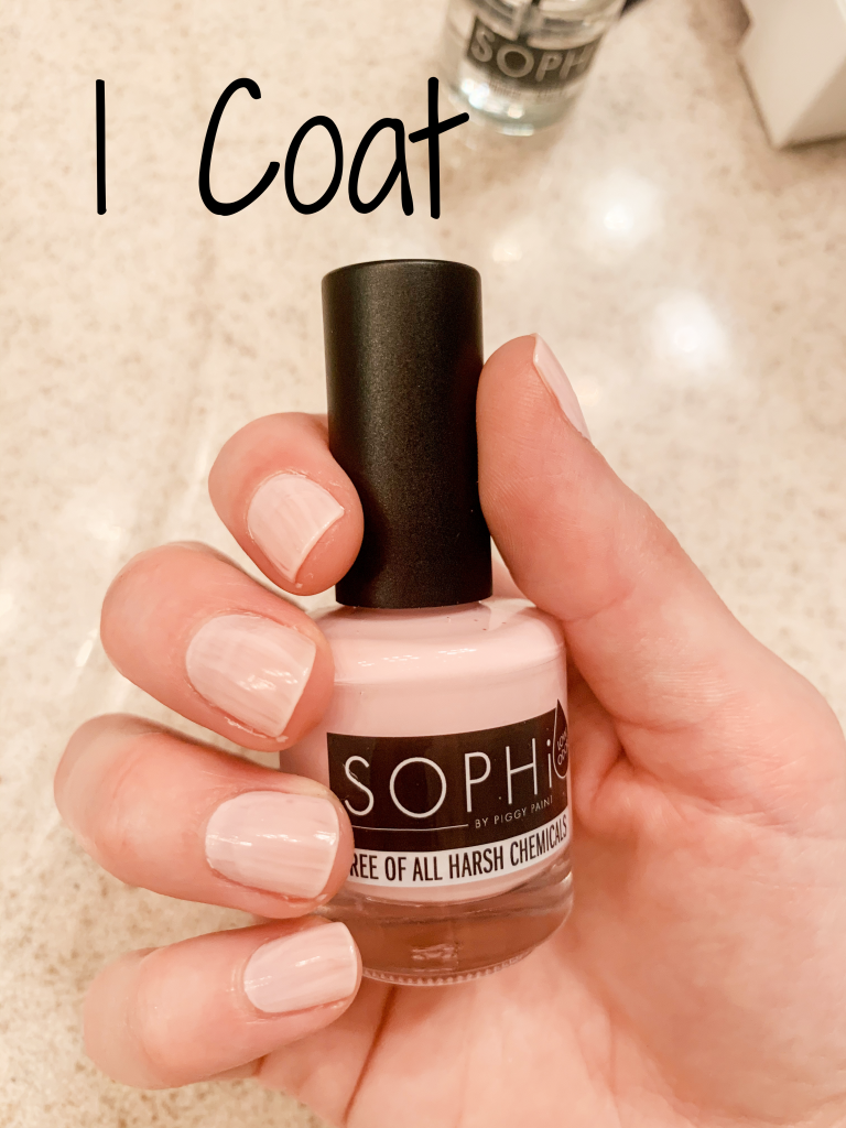 Photo of a hand holding SOPHi Nail Polish Morning Kisses bottle with one coat of polish on nails