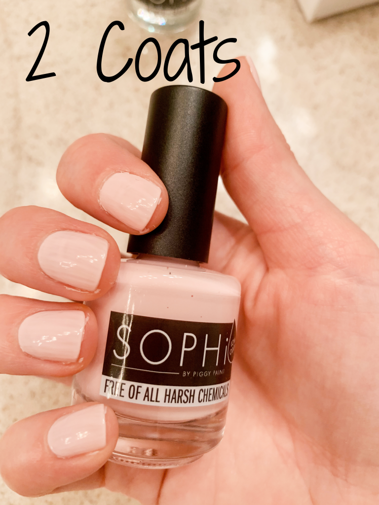 Photo of a hand holding SOPHi Nail Polish Morning Kisses bottle with two coats of polish on nails