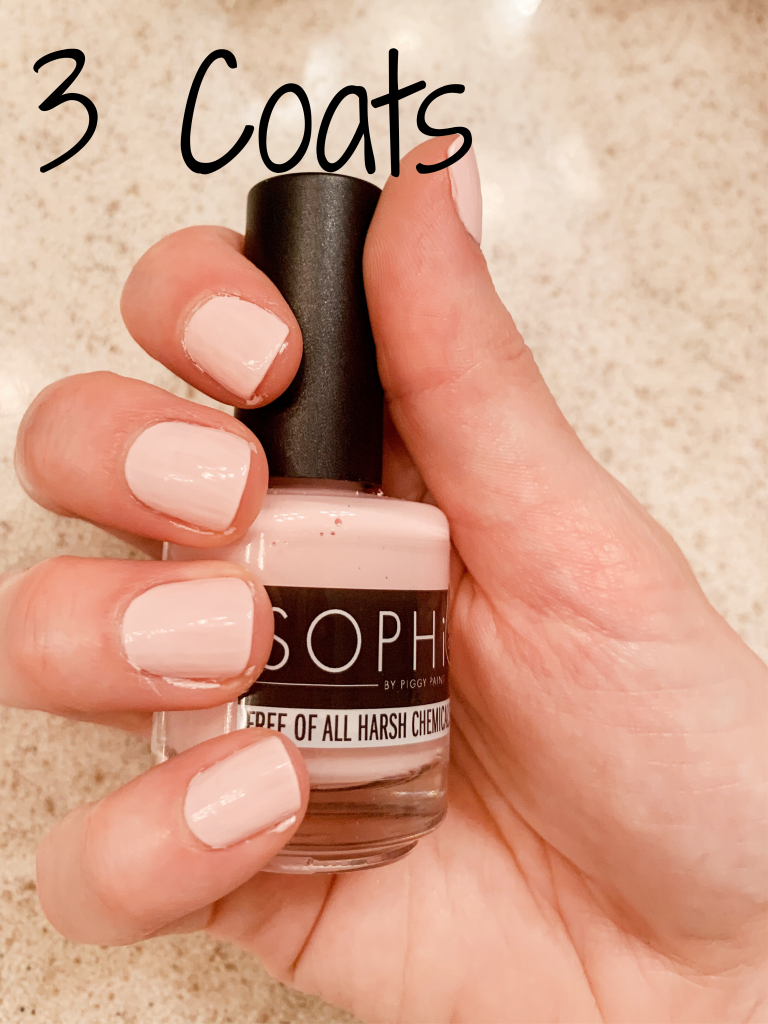 Photo of a hand holding SOPHi Nail Polish Morning Kisses bottle with three coats of polish on nails