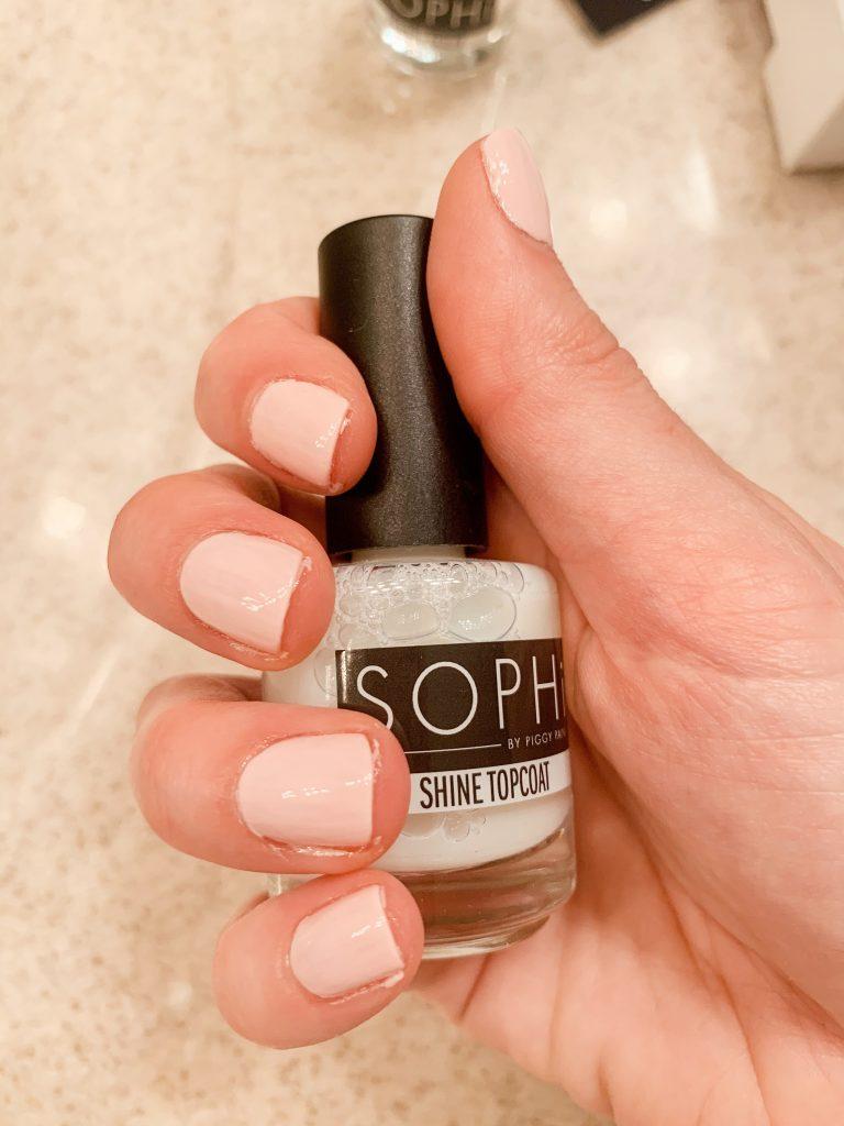 Photo of a hand holding SOPHi Nail Polish Shine Topcoat bottle
