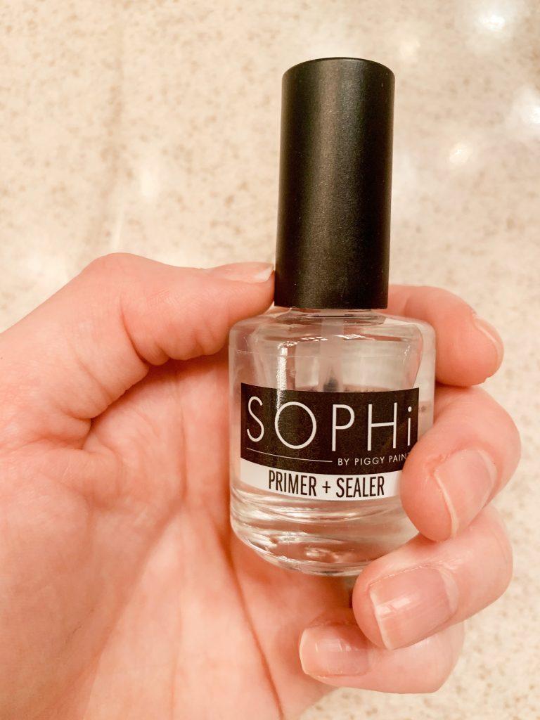 Photo of a hand holding SOPHi Nail Polish Primer + Sealer.